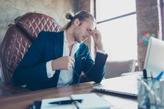 Portrait of tired overworked accountant sitting at his desktop i. N work place, holding hand on nose near eyes, closed eyes, putting off his glasses, having Stock Images