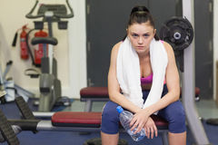 Portrait of a tired and thoughtful woman sitting in gym Royalty Free Stock Images