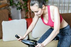 Portrait of a tired and weary young woman on a stationary bike after a workout. The concept of home fitness.  Stock Images
