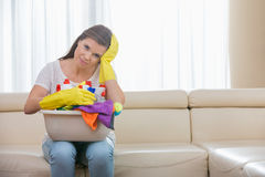 Portrait of tired woman with basket of cleaning supplies sitting on sofa at home stock photography