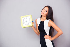 Portrait of a tired woman holding clock. Over gray background Royalty Free Stock Image