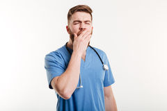Portrait of a tired young medical doctor yawning isolated royalty free stock photo
