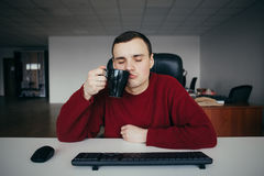 Portrait of a tired young office worker sitting with eyes closed and with a cup of coffee in hand. Royalty Free Stock Photography