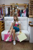 A full-length photo of a tired young woman holding her purchases and sitting on the clothing store background. Royalty Free Stock Images