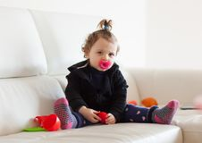 Portrait toddler baby girl playing on the sofa. Stock Photography