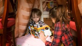 Portrait of toddler boy with book in tepee tent at bedroom. Portrait of toddler boy with book in tent at bedroom Royalty Free Stock Photo