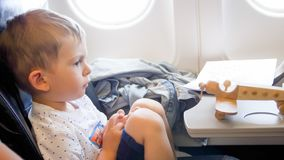 Portrait of little toddler boy flying in aircraft with toy wooden airplane royalty free stock photo