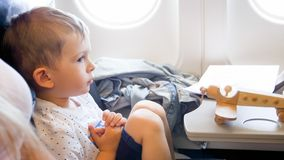 Portrait of cute toddler boy with wooden airplane miniature during long flight stock image