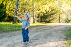 Toddler child outdoors. Rural scene with one year old baby boy with straw hat Stock Photos
