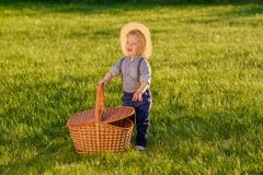 Toddler child outdoors. One year old baby boy wearing straw hat with picnic basket Royalty Free Stock Photography