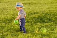 Toddler child outdoors. One year old baby boy wearing straw hat using watering can. Portrait of toddler child outdoors. Rural scene with one year old baby boy stock images