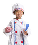 Portrait of a Toddler dressed as Chef. Holding an Oven Mitt and Spatula royalty free stock photography