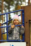 Portrait of a toddler girl playing in the autumn park playground, looking in the distance stock photography