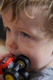 Portrait of toddler with red toy truck. Closeup portrait of blond boy holding a red toy truck close to his mouth Royalty Free Stock Photos