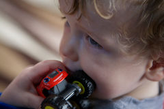 Portrait of toddler with red toy truck. Closeup portrait of small blond boy holding red toy truck close to his mouth royalty free stock images