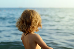 Portrait of a toddler white girl standing on a beach and looking horizon of the sea. Back view Stock Photo