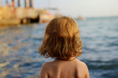 Portrait of toddler white girl standing on a beach and looking into horizon of the sea. Back view Stock Images