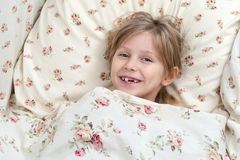 Portrait of a toothless girl in bed Stock Photo
