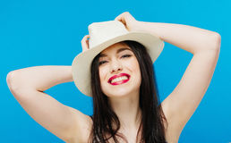 Portrait of Toothy Smiling Young Woman in Summer Hat Posing in Studio on Blue Background. Vacation Concept Stock Photos