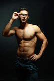 Portrait of topless macho man. Portrait of topless athletic macho man in glasses posing over black background Royalty Free Stock Images