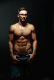 Portrait of topless macho man. Portrait of topless athletic macho man in glasses posing over black background Royalty Free Stock Photos