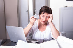 Portrait of a totally overworked woman in her home office Royalty Free Stock Photo