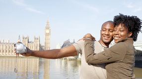 Portrait of tourist couple on Westminster. Panoramic view of a young african american couple taking pictures of themselves while on vacations in London Stock Photos