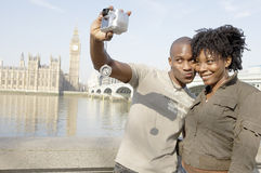Portrait of tourist couple on Westminster. Tourist couple taking a picture of themselves while visiting Big Ben in London city Royalty Free Stock Photo