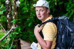 Portrait of a tourist in a hat with a backpack on a background. Of a green jungle Stock Photography