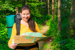 Portrait of a tourist with a map. In the forest Royalty Free Stock Image