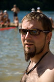 Portrait of tourist by ocean. Portrait of young male tourist with goatee beard stood by ocean in summer Stock Photos