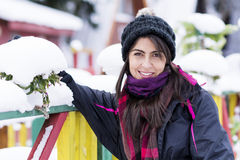 Portrait of a  tourists woman leaning on a colorful wooden fence with snow in the hand Royalty Free Stock Photos