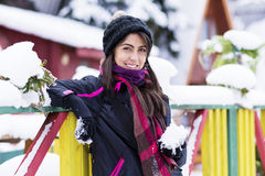 Portrait of a  tourists woman leaning on a colorful wooden fence with snow in the hand Stock Images