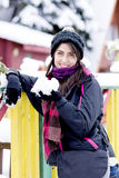 Portrait of a  tourists woman leaning on a colorful wooden fence with snow in the hand Stock Photo