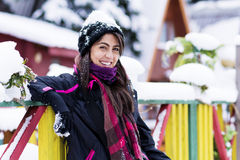 Portrait of a  tourists woman leaning on a colorful wooden fence with snow on a hat Stock Photos