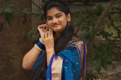 Traditional maharashtrian girl with a Saree-1. A portrait of a traditionally dressed Indian teenager adjusting her earrings Royalty Free Stock Photos