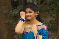 Traditional maharashtrian girl with a Saree-4. A portrait of a traditionally dressed Indian teenager touching her golden chain and showing her bangles Stock Photo
