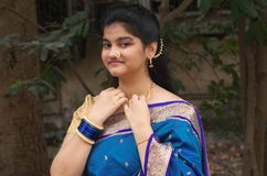 Traditional maharashtrian girl with a Saree-3. A portrait of a traditionally dressed Indian teenager touching her golden chain Royalty Free Stock Image