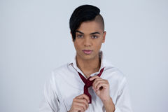 Portrait of transgender woman tying necktie Royalty Free Stock Images