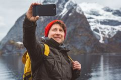 Portrait traveler man taking self-portrait a photo with a smartphone. Tourist in a yellow backpack standing on a royalty free stock photography