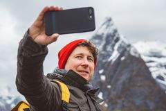 Portrait traveler man taking self-portrait a photo with a smartphone. Tourist in a yellow backpack standing on a stock images
