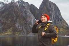 Portrait traveler man talking on mobile phone. Tourist in a yellow backpack standing on a background of a mountain and a royalty free stock photo