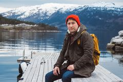 Portrait traveler man with a yellow backpack wearing a red hat sitting on wooden pier on the background of mountain and royalty free stock photography