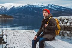 Portrait traveler man with a yellow backpack wearing a red hat sitting on wooden pier on the background of mountain and royalty free stock photo
