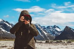 Portrait of a traveler is a professional photographer taking nature photo landscape. Wearing a yellow backpack in a cape stock photos