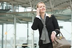 Portrait of a traveling business woman talking on mobile phone Stock Photos
