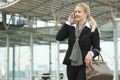 Portrait of a traveling business woman talking on mobile phone outdoors. Portrait of a traveling business woman talking on mobile phone outside Stock Photography