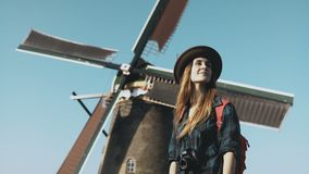 Portrait of traveller woman near old windmill. Incredible cinematic low angle. Girl in hat in front of farm mill. 4K. Successful happy travel. Young stock footage