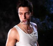 A portrait about a trendy cute guy who is smoking Royalty Free Stock Photo