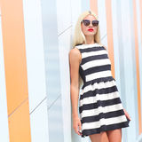 Portrait of trendy fashion girl in sunglasses. On the background color of orange wall Stock Photo